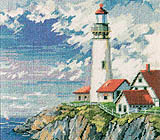 Fluffy white clouds and a deep blue sky set off a grouping of red-roofed buildings surrounding a towering lighthouse.